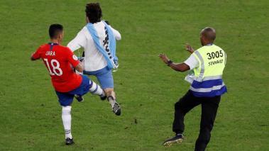 Gonzalo Jara (i) de Chile traba a un aficionado que invadió el campo, durante el partido Chile-Uruguay del Grupo C de la Copa América de Fútbol 2019, en el Estadio Maracanã de Río de Janeiro, Brasil, hoy 24 de junio de 2019. EFE