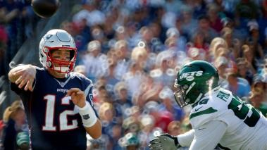 New England Patriots quarterback Tom Brady (L) makes a quick pass before being hit by New York Jets defensive end Kyle Phillips (R) during the second half of the New England Patriots defeat of the New York Jets at Gillette Stadium. EFE