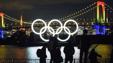 Varios fotógrafos observan los anillos olímpicos tras tomar fotos frente al lago del Odaiba Marine Park, en Tokio (Japón). Los Juegos Olímpicos de Tokio se disputarán del 23 de julio al 8 de agosto de 2021. EFE